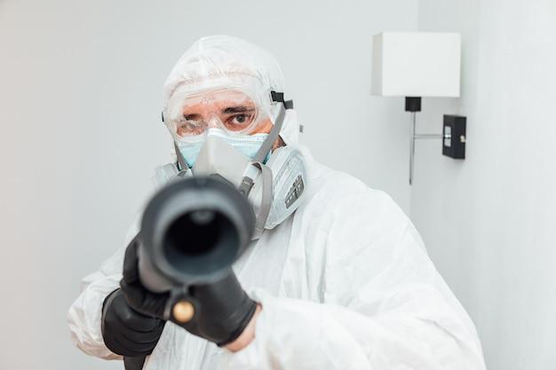 Man met pbm die de covid-19 desinfectiemachine op de camera richt. pandemisch gezondheidszorgconcept