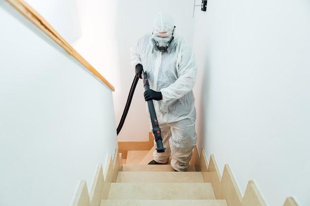 Man met pbm die de trap oploopt van een huis dat desinfecteert met covid-19. pandemisch gezondheidszorgconcept
