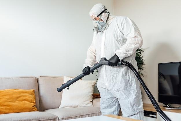 Man met pbm die de woonkamer van een huis desinfecteert met een covid-19 desinfectiemachine. pandemisch gezondheidszorgconcept