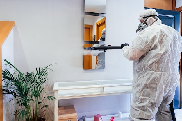 Man met pbm in een huis die een spiegel desinfecteert van covid-19. pandemisch gezondheidszorgconcept