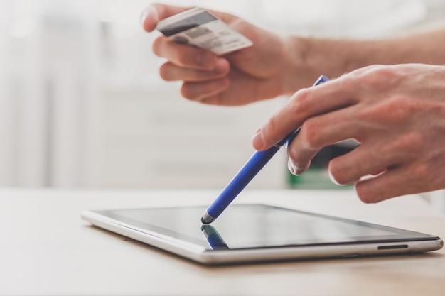 Man met pc-tablet met stylus en creditcard aan tafel, online winkelen