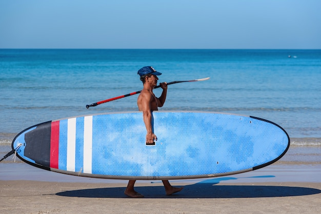 Man met pet op een strand met een blauwe surfplank. sportief en gezond levensstijlconcept.