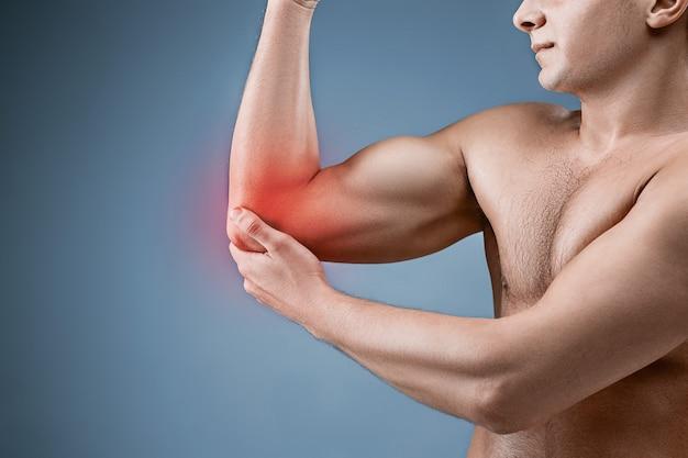 Man met pijn in elleboog. pijnbestrijding concept op grijze studio achtergrond