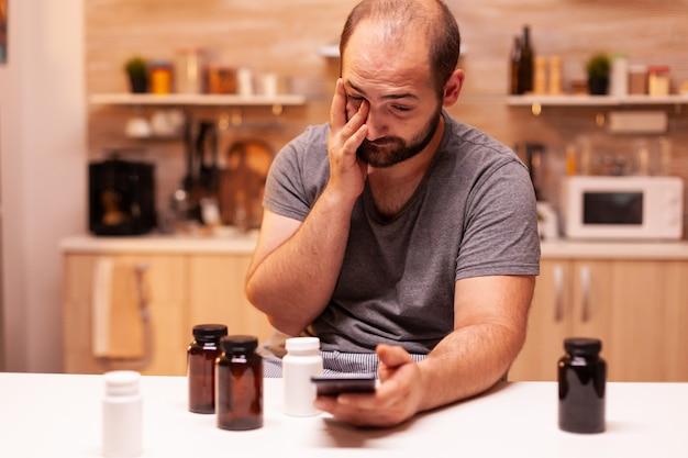 Man met pijn zoeken aan de telefoon medische behandeling. gestresst moe ongelukkig bezorgd onwel persoon die lijdt aan migraine, depressie, ziekte en angst zich uitgeput voelen met symptomen van duizeligheid
