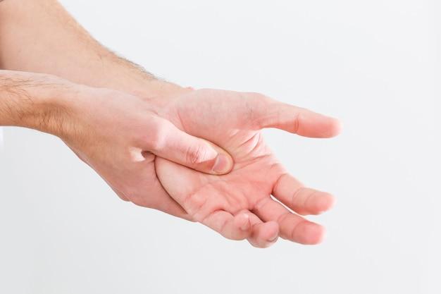 Man met pijnlijke en ontstoken jicht op zijn hand rond de duim.