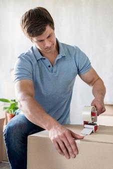 Man met plakband om doos in te pakken om te verhuizen