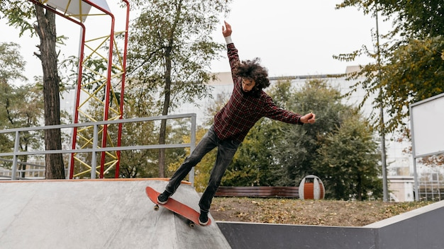 Man met plezier met skateboard buiten in het stadspark