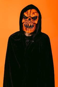 Man met pompoen latex masker en hooded fluwelen cape, op oranje achtergrond. halloween en dagen van het dode concept.