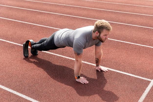 Man met prothetisch been doet hoge plank full shot