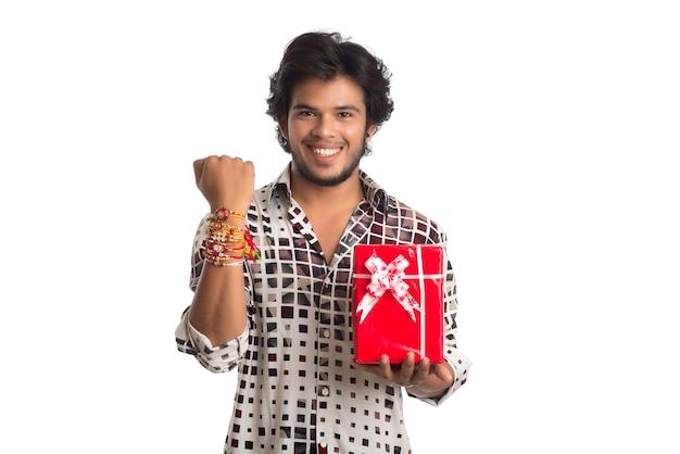 Man met rakhi op zijn hand met boodschappentassen en geschenkdoos ter gelegenheid van het raksha bandhan-festival.