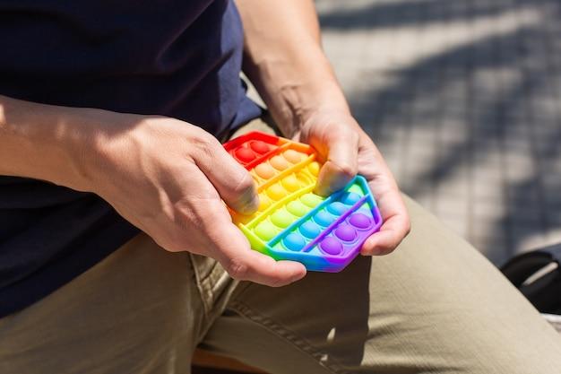 Man met regenboog anti-stress pop-it speelgoed buitenshuis