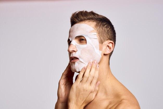 Man met reinigingsmasker op gezicht tegen zwart Premium Foto