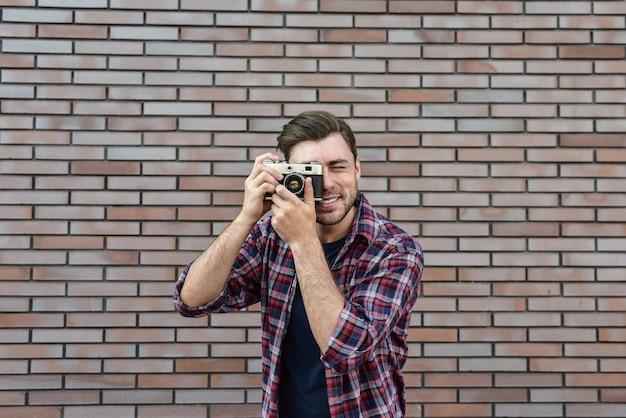 Man met retro fotocamera fashion travel lifestyle buiten terwijl je tegen een bakstenen muur achtergrond.