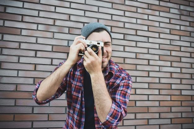 Man met retro fotocamera fashion travel lifestyle buiten terwijl je tegen een bakstenen muur staat.