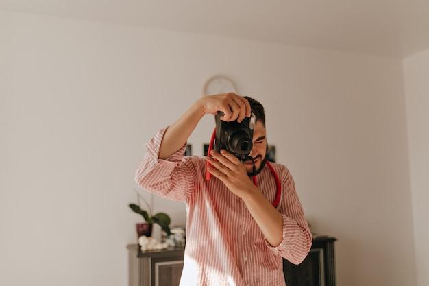 Man met ring aan zijn vinger maakt foto op camera. momentopname van donkerbruine man in gestreepte outfit in ruim appartement.