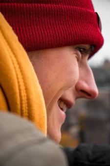 Man met rode gebreide pet en hoodie