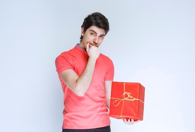 Man met rode geschenkdoos hand aan zijn mond brengen en denken.