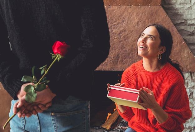 Man met roze bloem voor vrouw achter rug
