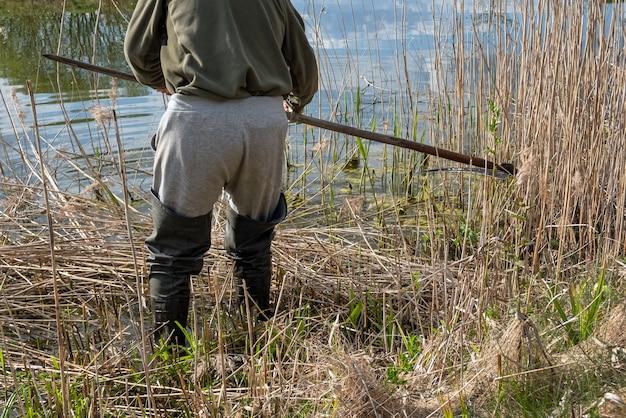 Man met rubberen laarzen die bovengronds raast langs de oever van het meer. man die biezen snijdt met oude zeis buiten op een zonnige dag