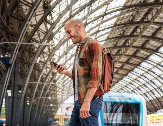 Man met rugzak mobiel gebruiken