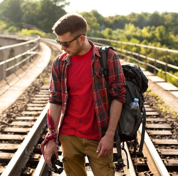 Man met rugzak op treinrail