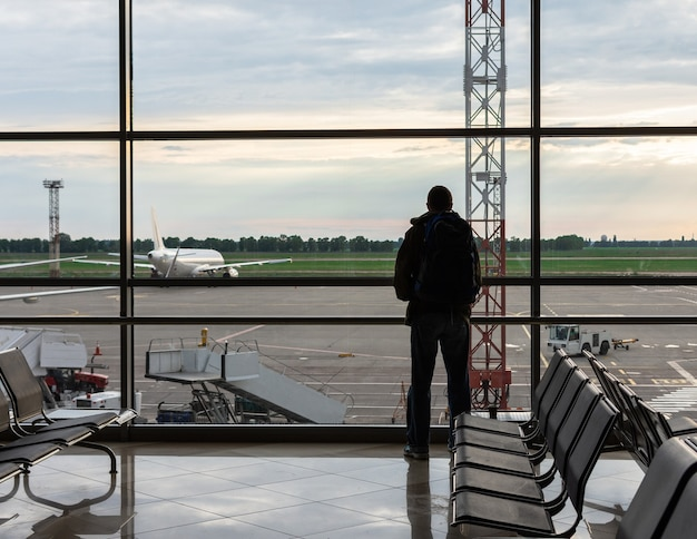 Man met rugzak op zijn schouders kijkt uit het raam naar de vliegtuigen op de luchthaven, luchttoerisme