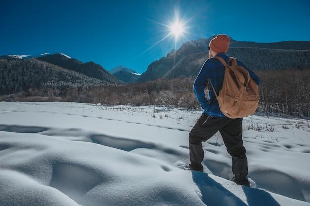 Man met rugzak trekking in de bergen. koud weer, sneeuw op heuvels. winterwandelen. zon en sneeuw