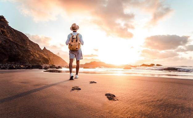 Man met rugzak wandelen op het strand bij zonsondergang