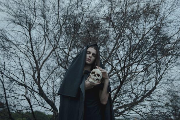 Man met schedel omringd door herfst takken