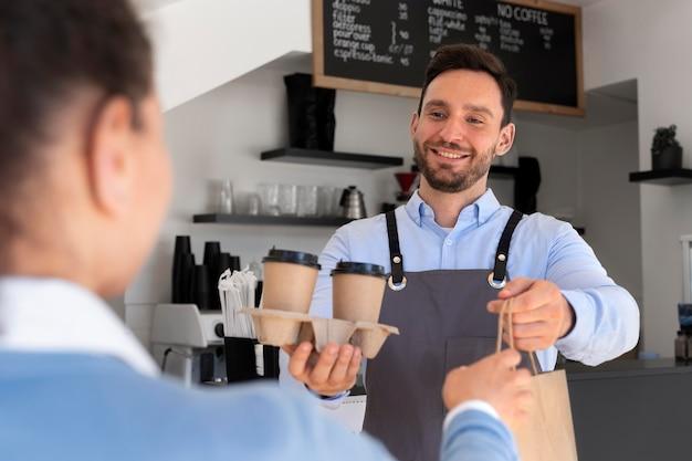 Man met schort die afhaalmaaltijden aanbiedt aan vrouwelijke klant