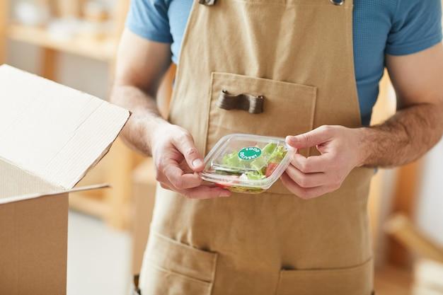 Man met schort verpakking individuele etensporties, voedselbezorgingsmedewerker
