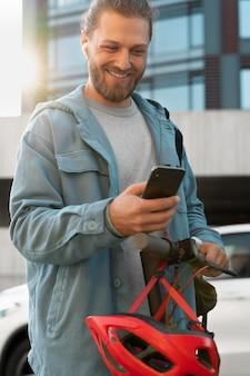 Man met scooter die naar zijn telefoon kijkt