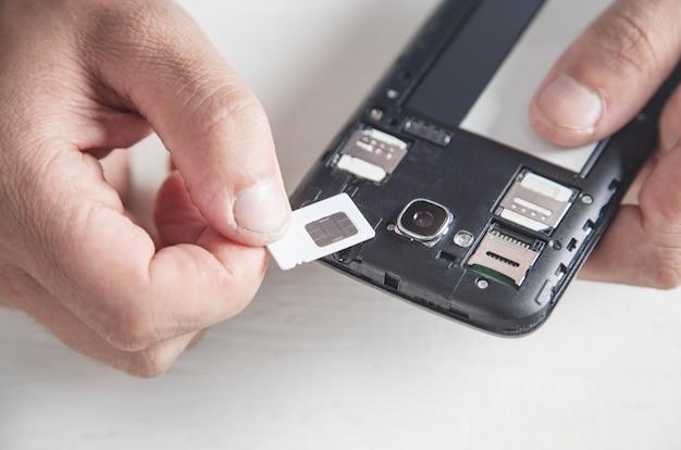 Man met sim-kaart met smartphone.