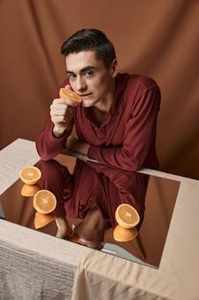 Man met sinaasappels op de spiegel op het tafelblad bekijken stof achtergrond. hoge kwaliteit foto