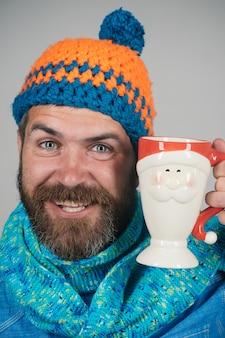 Man met sjaal en muts houdt kop warme koffie of thee in de hand, knappe, vrolijke winterman met kop