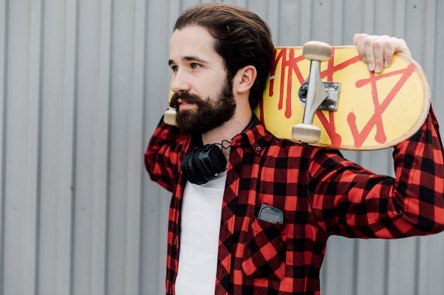Man met skateboard en koptelefoon