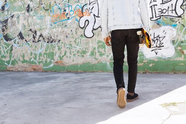 Man met skateboard in stedelijke omgeving