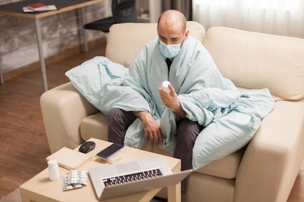 Man met slechte gezondheid met pillenfles gewikkeld in deken tijdens videogesprek in tijd van zelfisolatie.