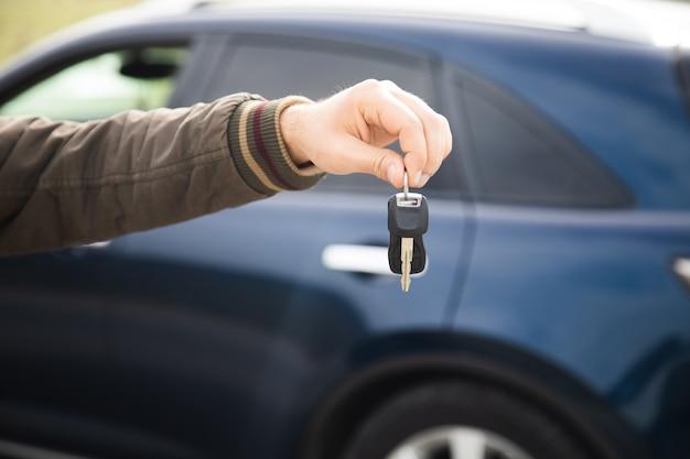 Man met sleutels op het oppervlak van een blauwe auto