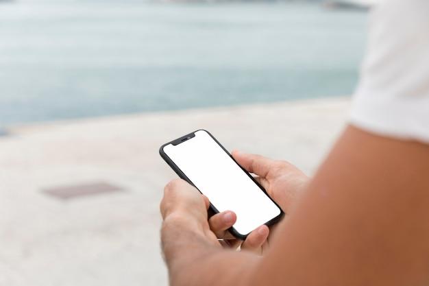 Man met smartphone buitenshuis met kopie ruimte