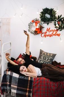Man met smartphone en slapende vrouw op bed