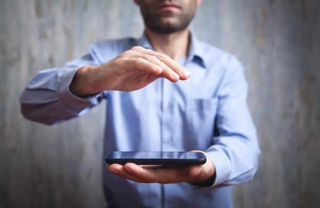 Man met smartphone met een beschermgebaar. technologie concept