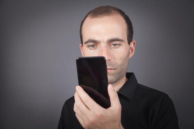 Man met smartphone op kantoor.