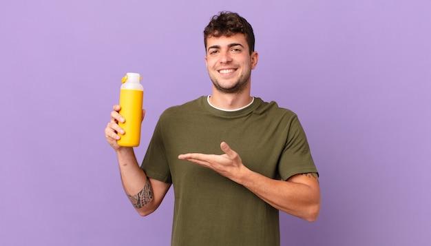 Man met smoothy die vrolijk lacht, zich gelukkig voelt en een concept in kopieerruimte laat zien met palm van hand