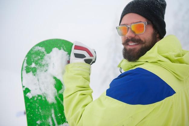 Man met snowboard in de winter