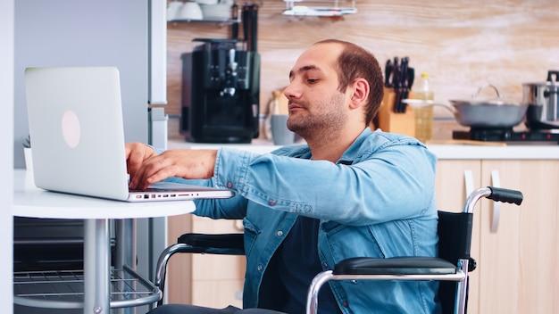 Man met speciale behoeften in rolstoel die aan laptop in keuken werkt. zakelijke man met verlamming handicap handicap gehandicapte moeilijkheden met werken na een ongeval met internet online videogesprek co