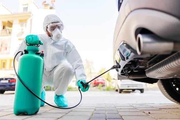 Man met sproeier met ontsmettingsmiddel en auto spuiten. bescherming tegen coronavirusconcept.