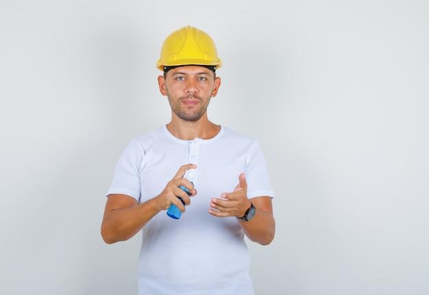 Man met spuitfles voor het reinigen van handen in t-shirt, helm en voorzichtig, vooraanzicht kijken.