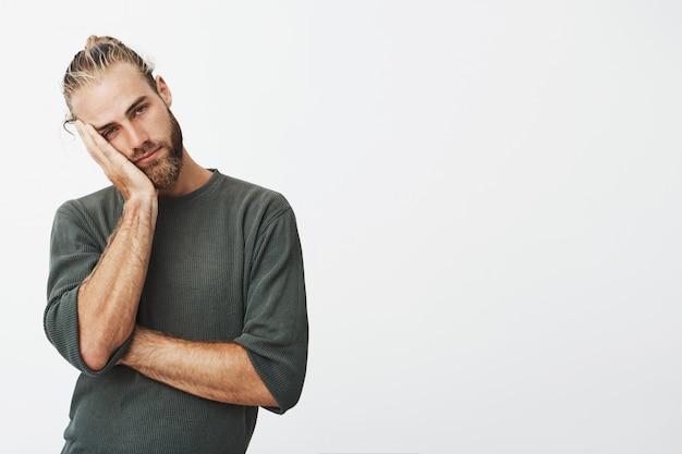 Man met stijlvolle kapsel en baard hoofd houden met hand moe