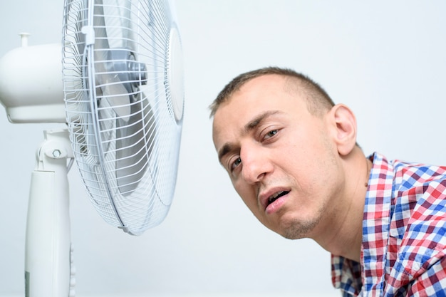 Man met stoppels op zijn gezicht heeft last van de hitte en probeert af te koelen bij de ventilator.